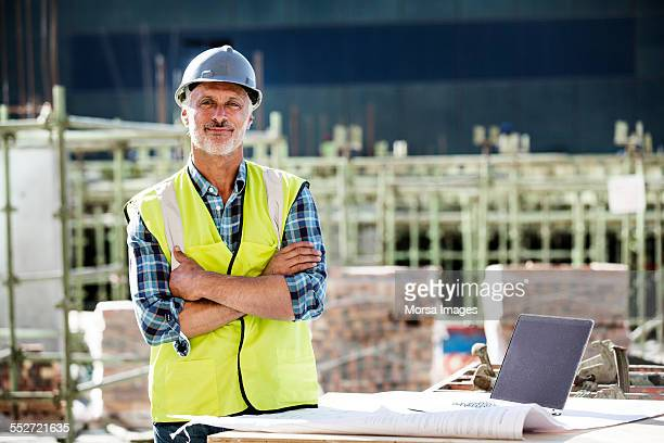 confident architect standing at construction site - work helmet stock pictures, royalty-free photos & images