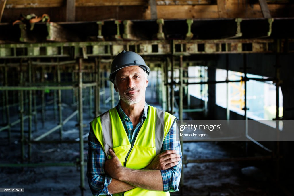 Confident architect standing at construction site : Stock Photo