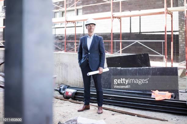 confident architect wearing hard hat standing on construction site - architekturberuf stock-fotos und bilder