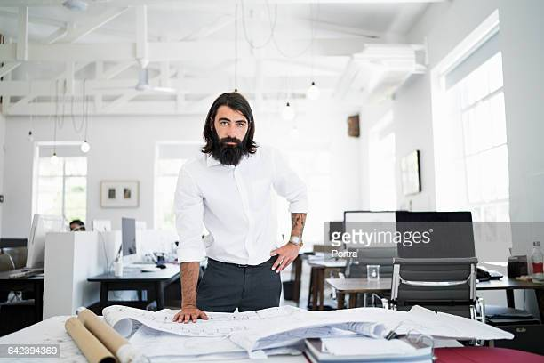 Confident architect with blueprints in office