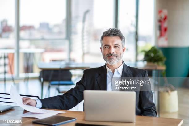 zuversichtlicher argentinischer reifer geschäftsmann am schreibtisch im stadtbüro, buenos aires - finanzen und wirtschaft stock-fotos und bilder