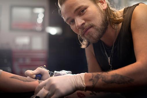 Confident artist tattooing woman's hand - gettyimageskorea