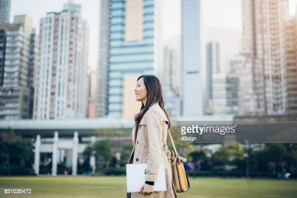 Confident Asian businesswoman carrying documents in the city against urban cityscape