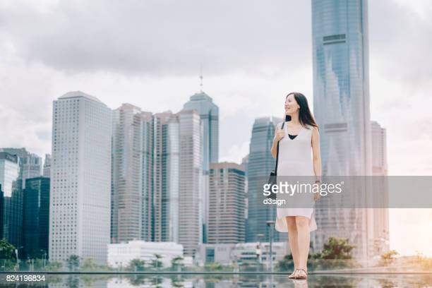 Confident Asian businesswoman in city, against financial skyscrapers and cityscape of Central, Hong Kong