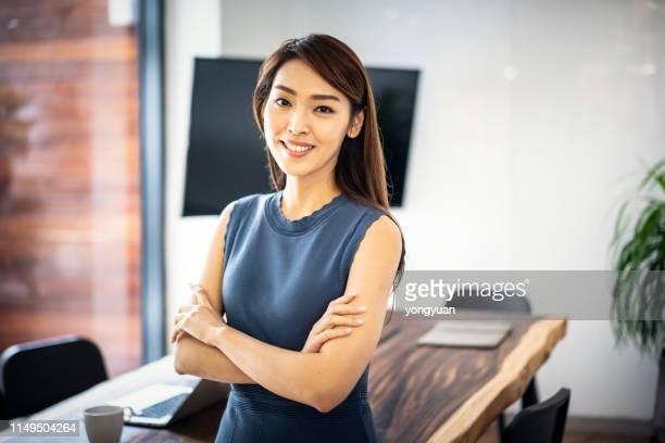 confident asian businesswoman in office - mezzo busto foto e immagini stock