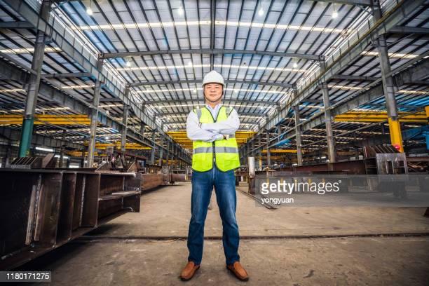 zelfverzekerde aziatische ingenieur in een staalfabriek - opscheppen stockfoto's en -beelden