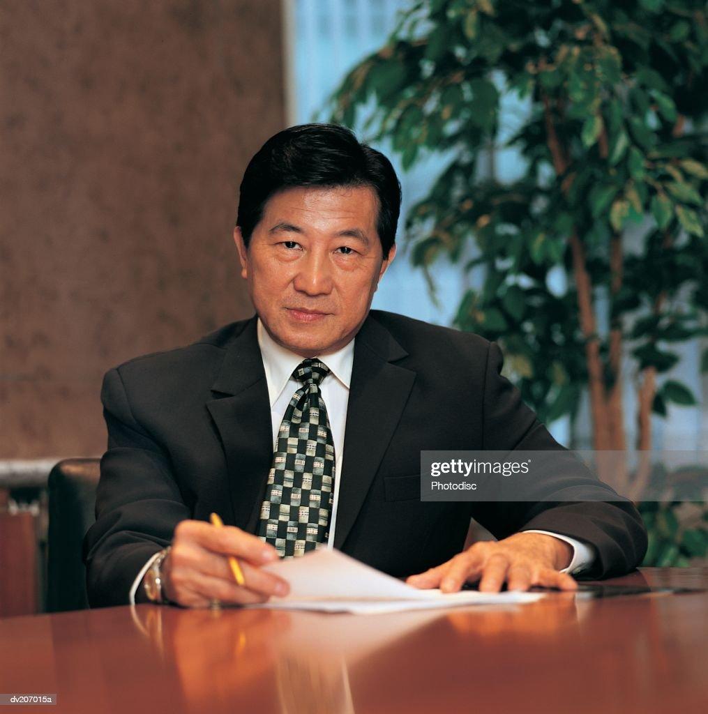 Confident Asian man at desk : Stock Photo
