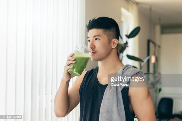 confident asian man drinking protein shake after workout - juice drink stock pictures, royalty-free photos & images