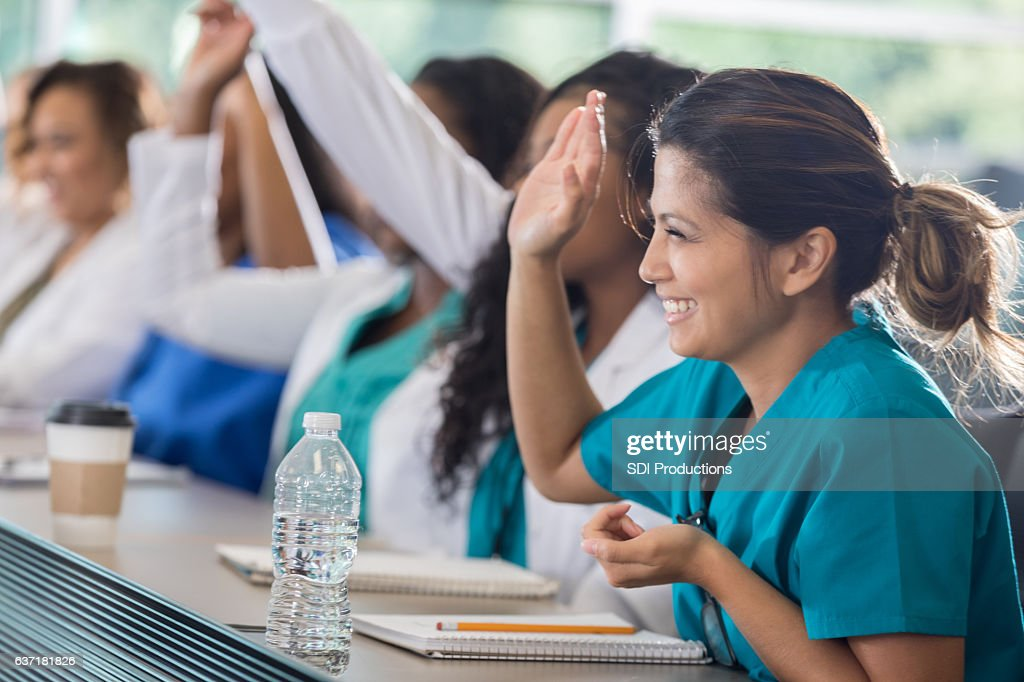 Confident Asian medical student raises hand in class : Stock Photo