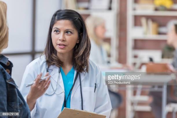 自信を持ってアジア医師が女性患者と協議します。