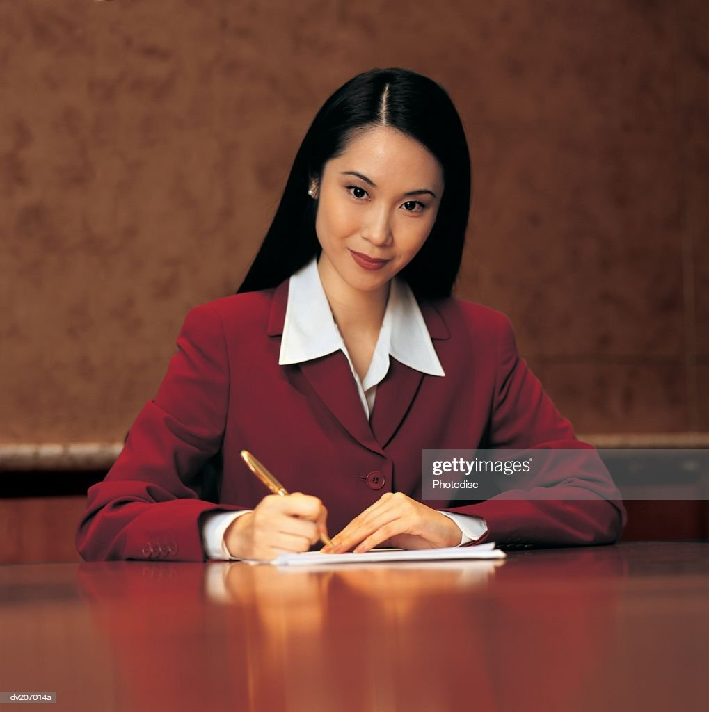 Confident Asian woman at desk : Stock Photo