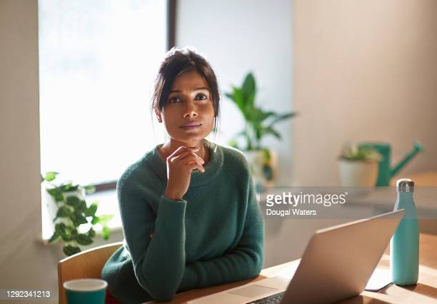 confident asian woman in green jumper at home with laptop. - asian and indian ethnicities stock pictures, royalty-free photos & images