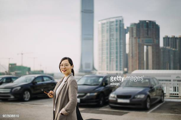 Confident Asian woman with smartphone against urban cityscape
