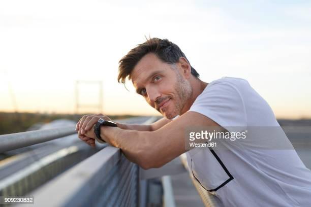 confident athlete leaning on railing - geländer stock-fotos und bilder