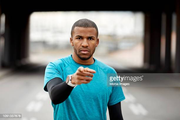 confident athlete pointing while standing in city - pointing stock pictures, royalty-free photos & images