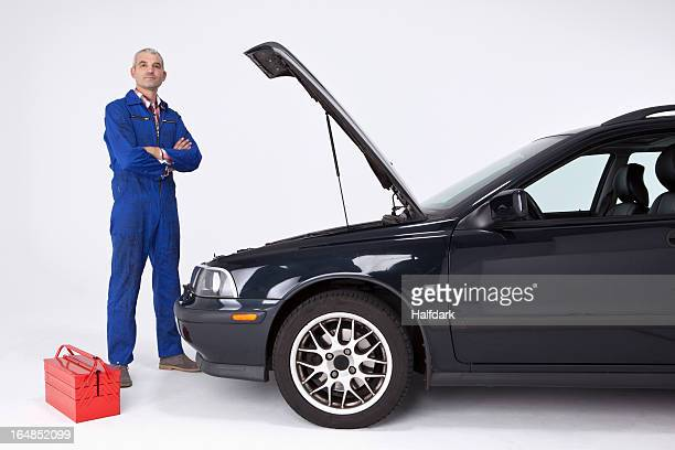 A confident auto mechanic standing with arms crossed next to a car with open hood