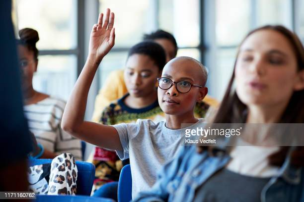 confident bald female student with arms raised - q and a stock pictures, royalty-free photos & images