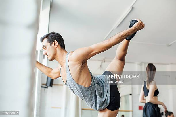 Confident ballet dancer stretching leg in studio