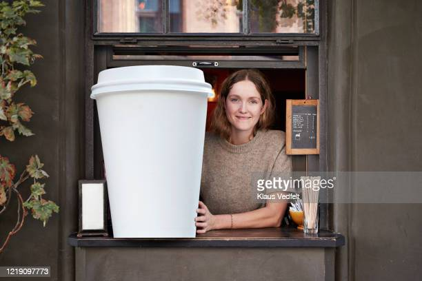 confident barista holding disposable coffee cup at take out counter of cafe - funny customer service stock pictures, royalty-free photos & images