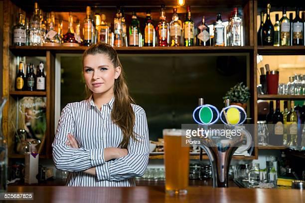Confident bartender standing in restaurant