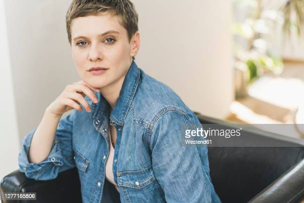 confident beautiful woman with hand on chin sitting over armchair at home - shorthair stock pictures, royalty-free photos & images