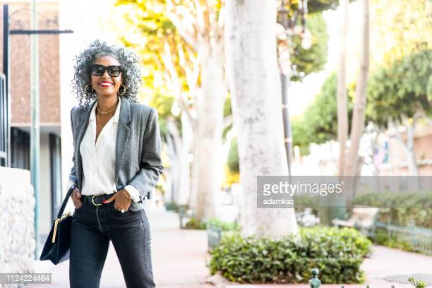 confident black woman walking in city - black purse stock pictures, royalty-free photos & images