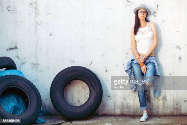 Zuversichtlich Boho trendige Mädchen an die Wand gelehnt