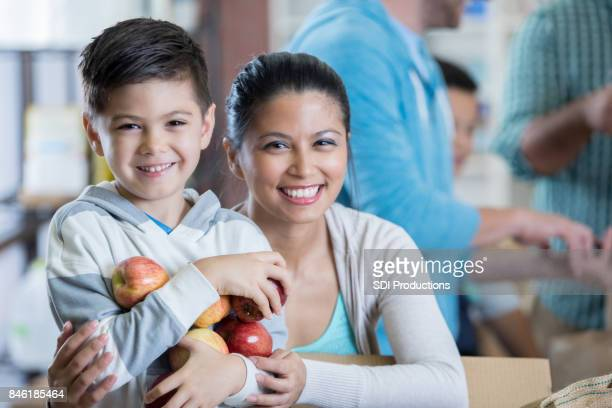confident boy and his mom donate food to homeless shelter - homeless shelter stock pictures, royalty-free photos & images