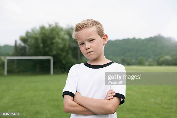 confident boy in soccer jersey on soccer pitch - fußballtrikot stock-fotos und bilder