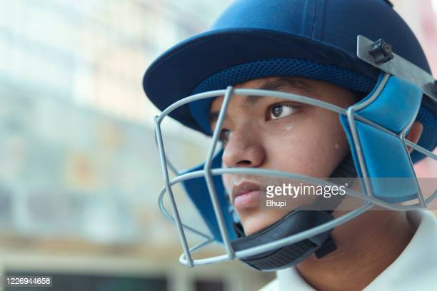 zuversichtlicher junge trägt crickethelm und bereit zum spielen. - mannschaftssport stock-fotos und bilder