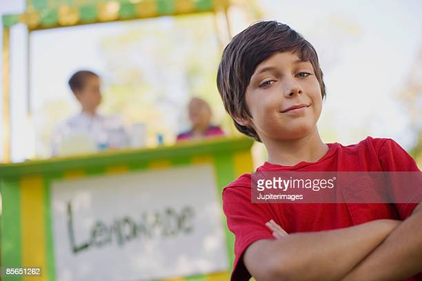 Confident boy with lemonade stand