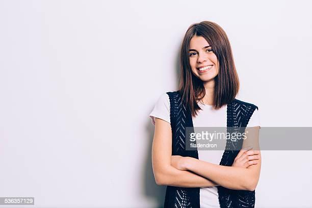 Confiant brunette s'appuyant sur le mur