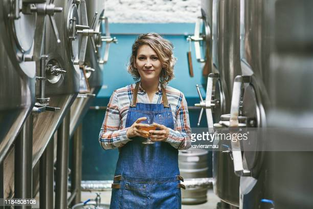 confident buenos aires craft beer expert standing in brewery - brewery stock pictures, royalty-free photos & images