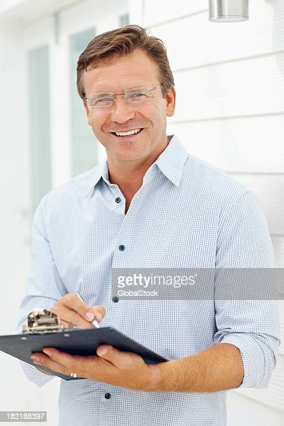 Confident business man holding clipboard