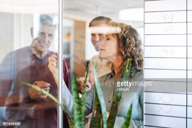 gente de negocios seguros sobre plan en vidrio - equidad de genero fotografías e imágenes de stock