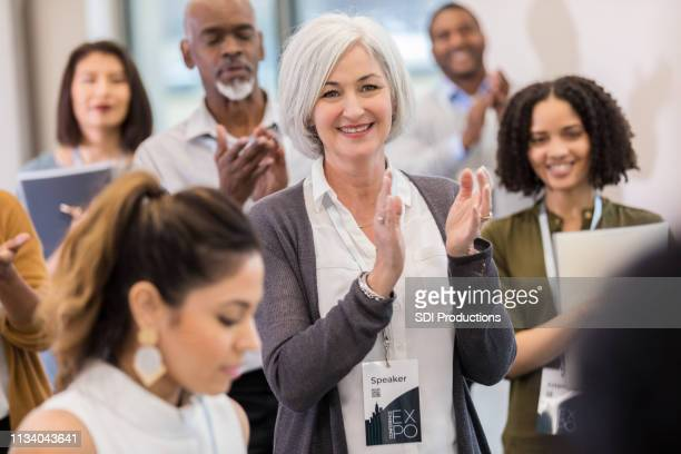 confident business woman applauds during conference - summit meeting stock pictures, royalty-free photos & images