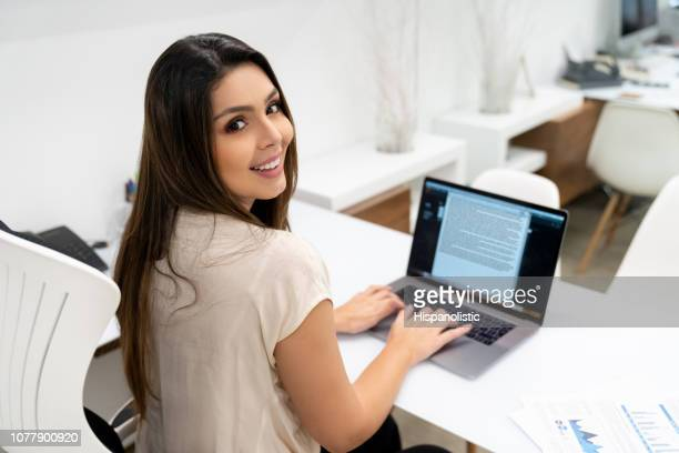 confident business woman at her office typing something on laptop while facing camera very happy - hispanolistic stock photos and pictures