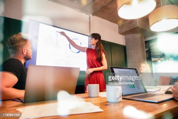 confident business woman presents quarterly progress in meeting using a large display screen - solutions stock pictures, royalty-free photos & images