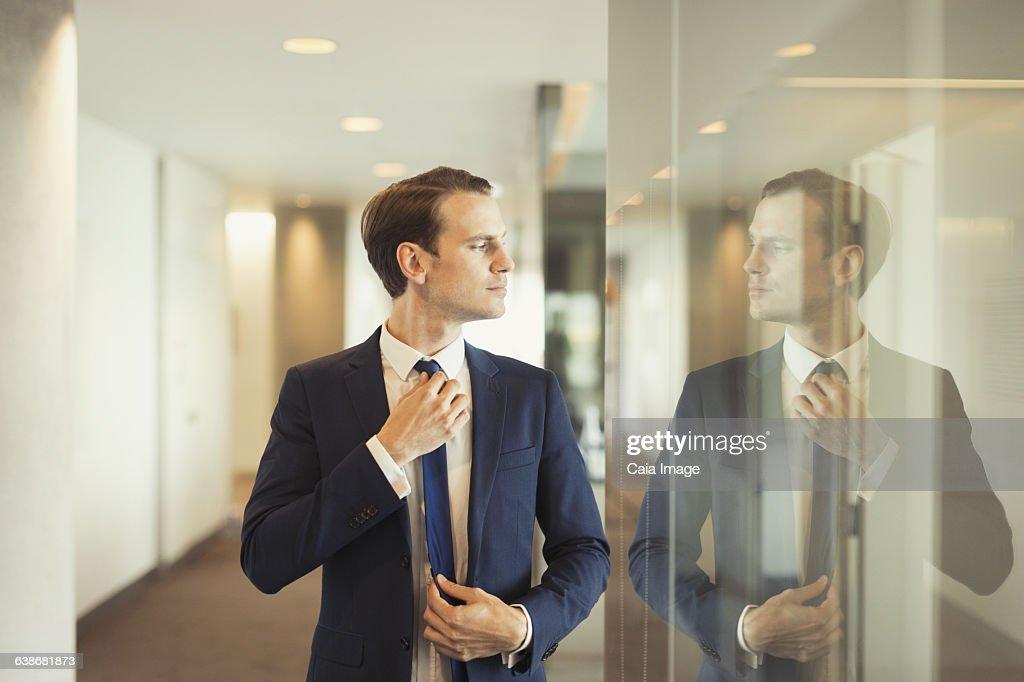 Confident businessman adjusting tie in office corridor : Stock Photo