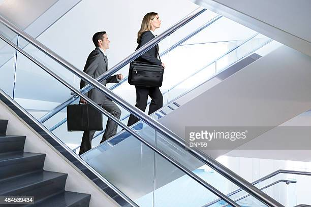 Confident Businessman And Businesswoman walking up flight of stairs