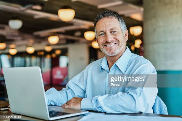 confident businessman at coworking space - 45 49 years stock pictures, royalty-free photos & images