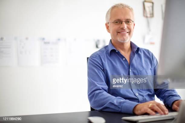 zekere zakenman bij zijn bureau - mid volwassen stockfoto's en -beelden