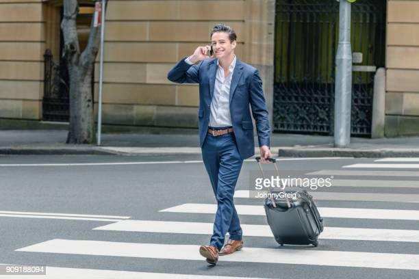 Zuversichtlich Geschäftsmann Kreuzung Straße mit fahrbaren Koffer auf dem Handy