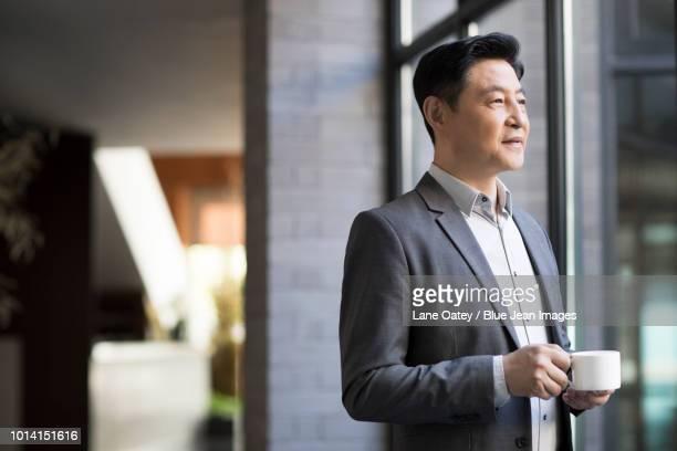confident businessman drinking coffee - einzelner mann über 40 stock-fotos und bilder