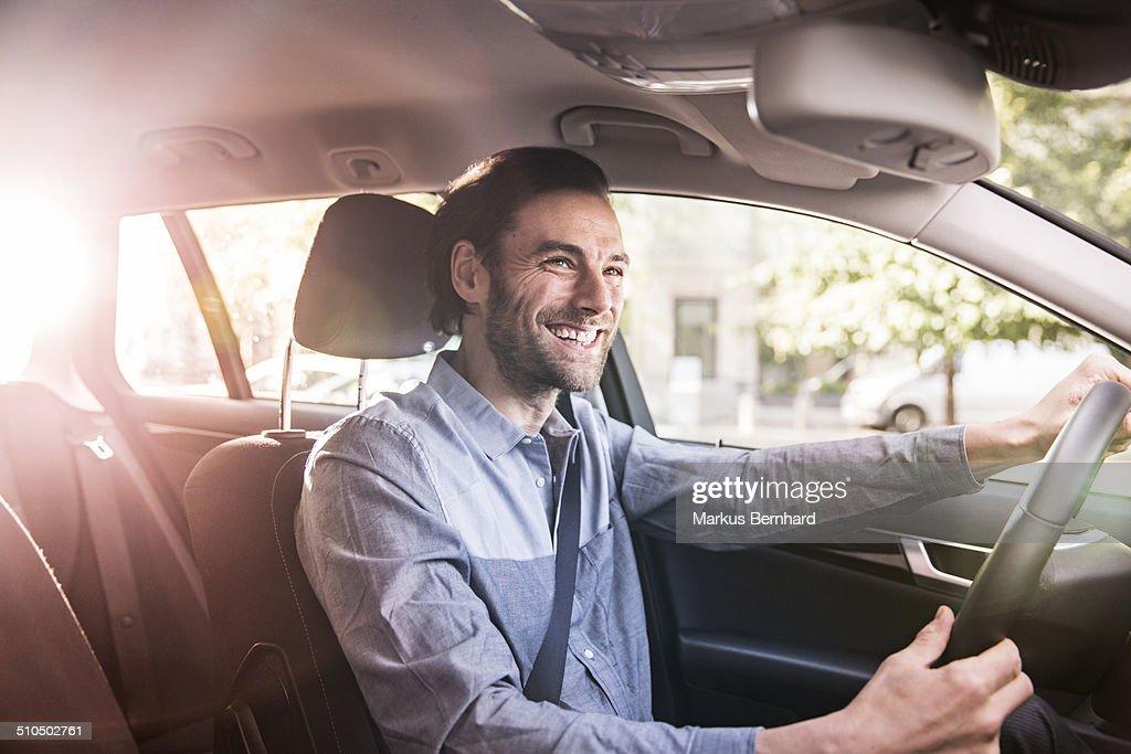Confident businessman driving his car. : ストックフォト