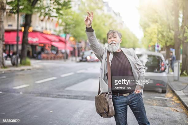 Confident businessman hailing taxi on street