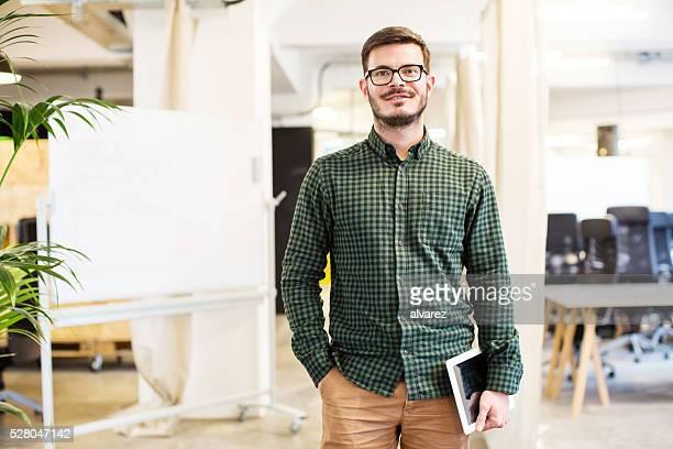 zuversichtlich geschäftsmann halten digitaltablett im büro - hände in den taschen stock-fotos und bilder