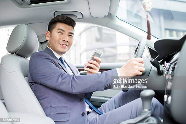 Confident businessman holding smart phone in a car