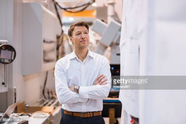 Confident businessman in factory looking around