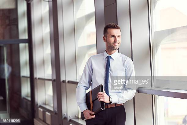 Confident businessman in office, holding a briefcase